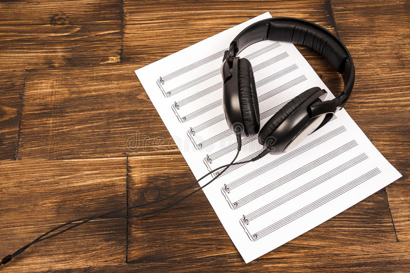 Fones de ouvido profissionais pretos grandes que encontram-se na folha de música no fundo de madeira fotos de stock royalty free