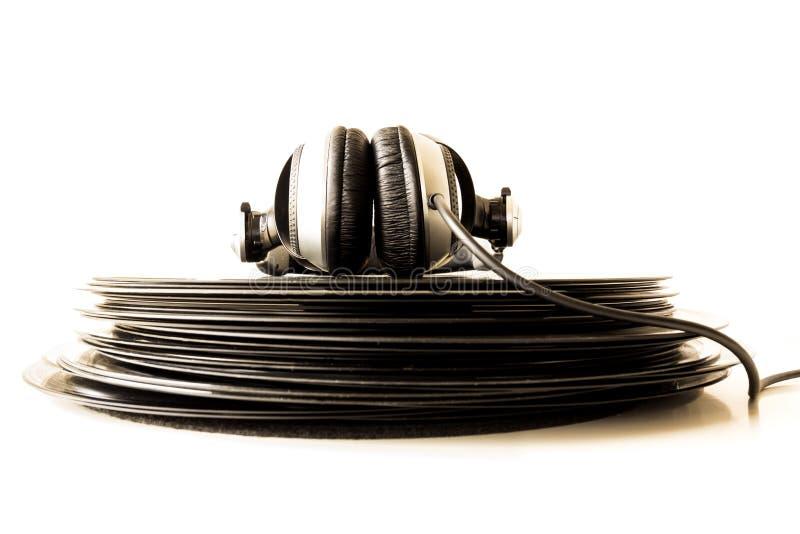 Fones de ouvido que encontram-se na pilha de registros de vinil foto de stock