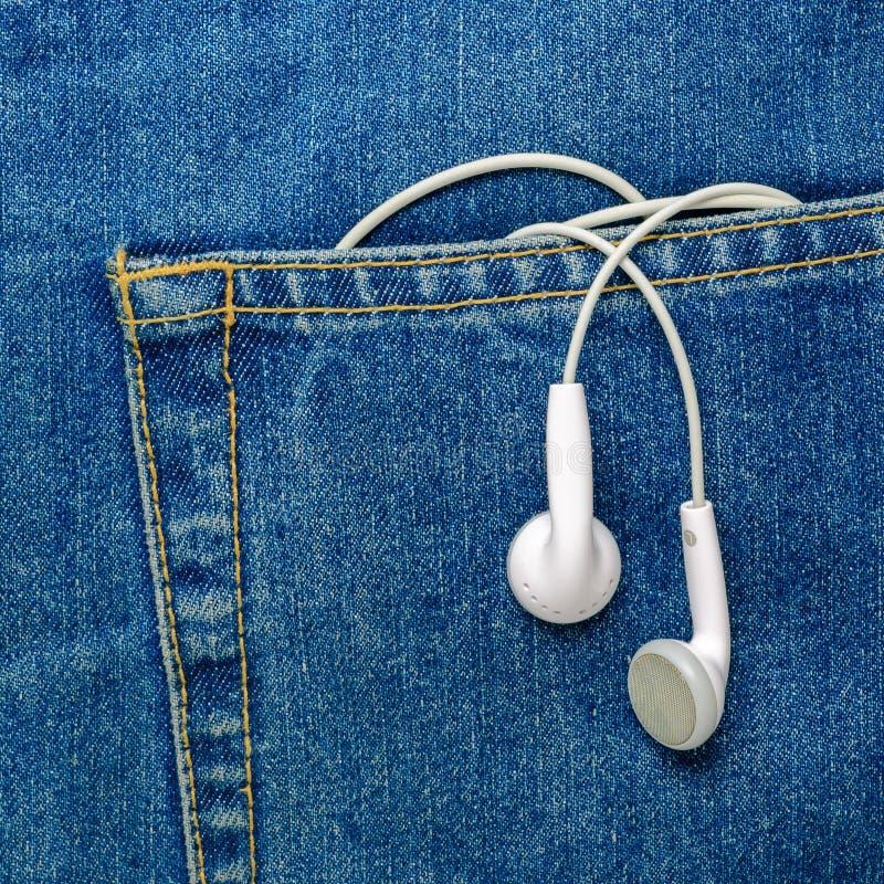 Fones de ouvido que penduram fora de um bolso das calças de brim foto de stock royalty free