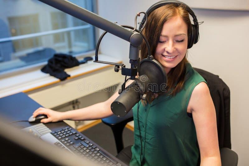 Fones de ouvido de rádio de Smiling While Wearing do jóquei no estúdio fotografia de stock