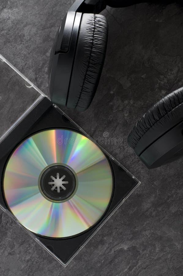 Fones de ouvido sem fio com o disco compacto no granito imagens de stock royalty free