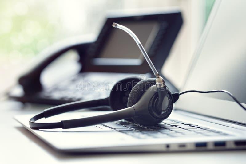 Fones de ouvido telefone e portátil dos auriculares no centro de atendimento foto de stock