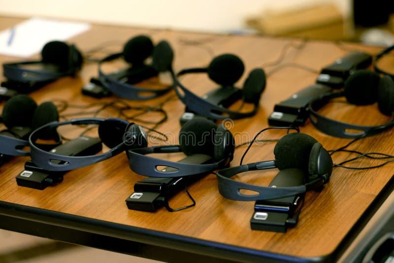 Fones de ouvido usados para o equipamento simultâneo da tradução foto de stock