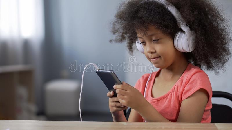 Fones de ouvido vestindo da criança africana adorável da menina, escutando a música no telefone celular foto de stock royalty free