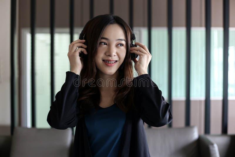 Fones de ouvido vestindo da mulher asiática bonita bonita e música de escuta fotografia de stock