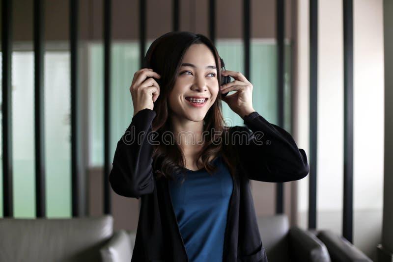 Fones de ouvido vestindo da mulher asiática bonita bonita e música de escuta fotografia de stock royalty free