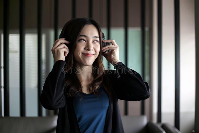 Fones de ouvido vestindo da mulher asiática bonita bonita e música de escuta imagem de stock