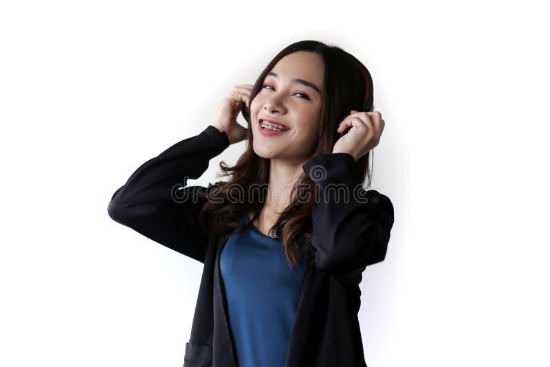 Fones de ouvido vestindo da mulher asiática bonita bonita e música de escuta no fundo branco fotografia de stock royalty free