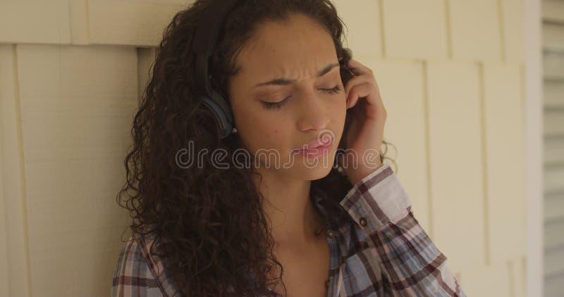 Fones de ouvido vestindo de uma mulher latino-americano nova bonita imagens de stock