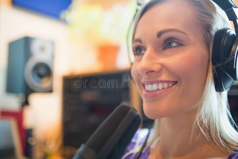 Fones de ouvido vestindo do anfitrião de rádio novo usando o estúdio do microfone fotografia de stock