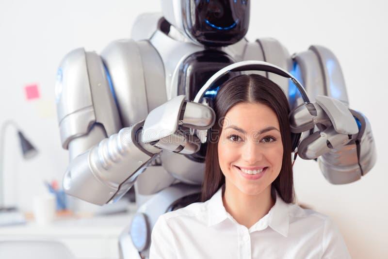 Fones de ouvido vestindo do robô nas orelhas da menina de sorriso fotos de stock royalty free