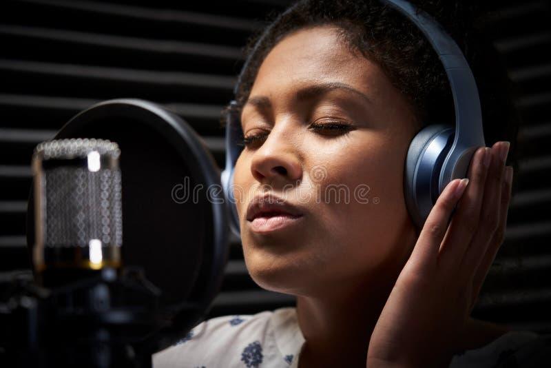 Fones de ouvido vestindo do vocalista fêmea que cantam no microfone no estúdio de gravação imagem de stock