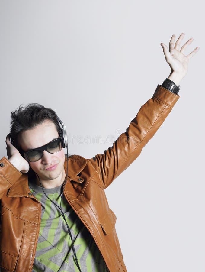 Fones de ouvido vestindo e óculos de sol do homem fresco foto de stock