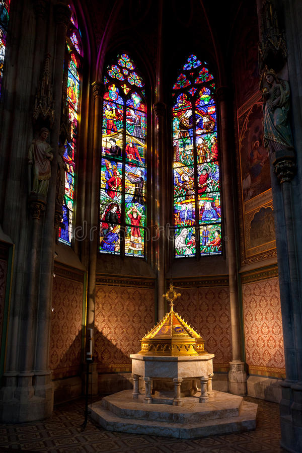 Font Baptistery , Votive church, Vienna, Austria. Baptismal font in the baptistery chapel and stained glass or glass in lead window in the neo-Gothic Votive stock photos