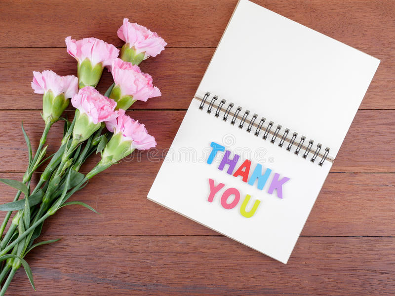 Font Thank you on blank notebook and bouquet of Carnation flower royalty free stock photos
