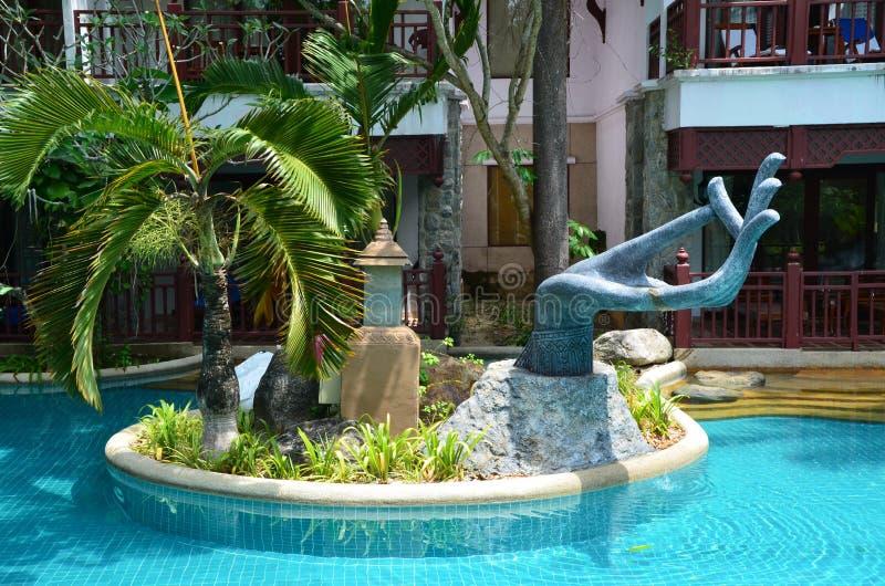 Fontain in einem Pool mit Blumen und Palme um sie stockbilder