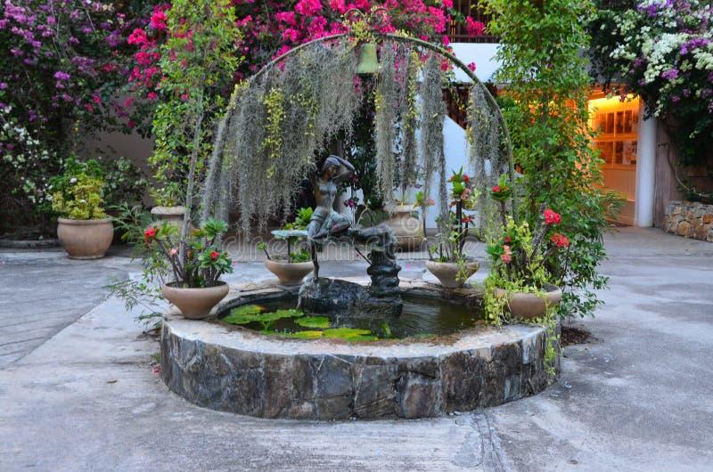 Fontain med blommor och träd runt om den royaltyfri bild