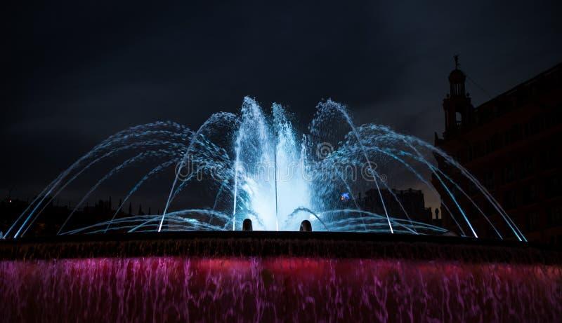 Fontaine d'eau color?e la nuit images stock