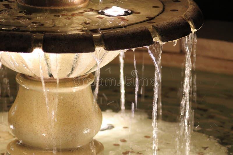 Fontaine d'eau lumineuse avec des pièces de monnaie photo libre de droits