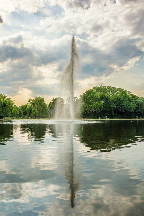Fontaine d'eau reflétée dans le lac d'un parc de ville photo stock