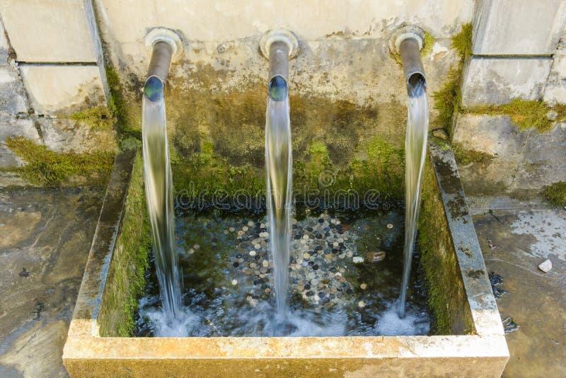 Fontaine de l'eau de source avec des pièces de monnaie, parc national de Strandja, Bulg photos stock