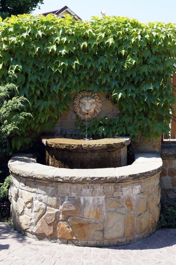 Fontaine de pierre décorative près du mur photo stock