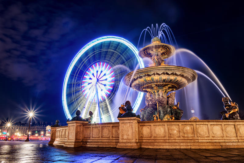 Fontaine des Mers and Ferris wheel at night. Fontaine des Mers, and Ferris wheel at the Place de la Concorde in Paris royalty free stock photography