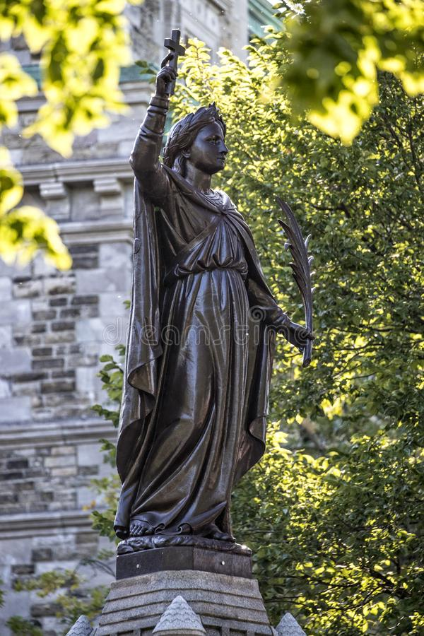 Fontaine Gothique in Quebec City Canada. Holding cross with tree branches framing statue stock images