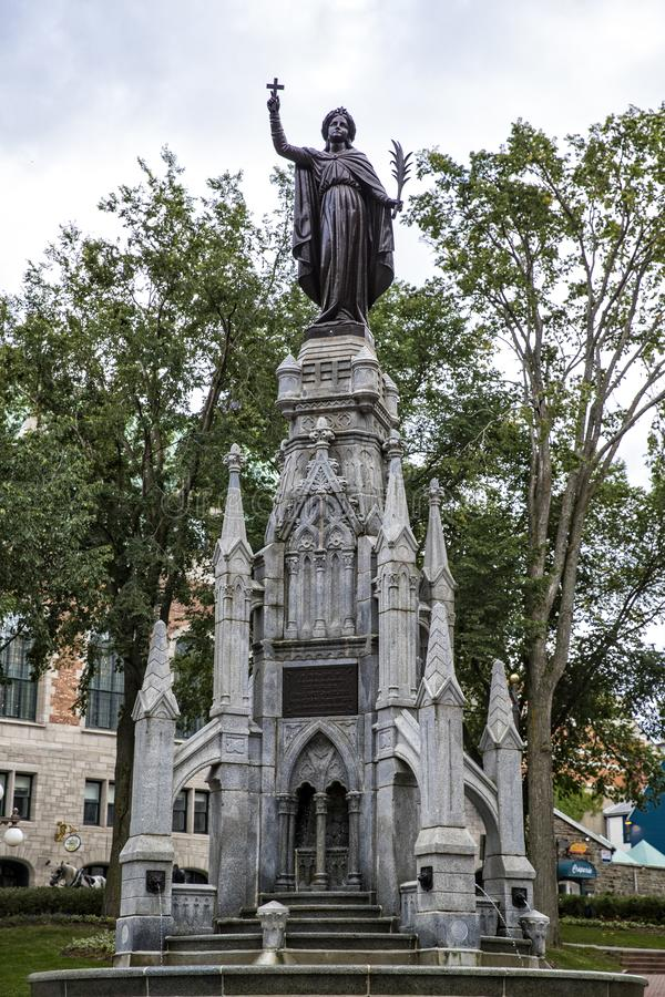 Fontaine Gothique in Quebec City Canada in front view. Front view of Fontaine Gothique in Quebec City Canada holding cross with tree branches framing statue royalty free stock photos