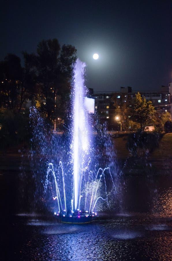 Fontaine lumineuse colorée au milieu du lac la nuit avec la pleine lune photos libres de droits