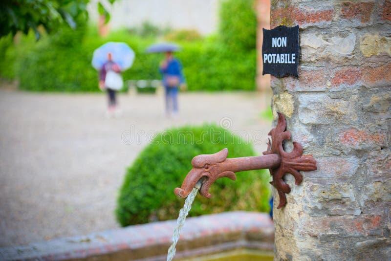 Fontaine médiévale avec des métiers de robinet et signe pas l'eau potable image libre de droits