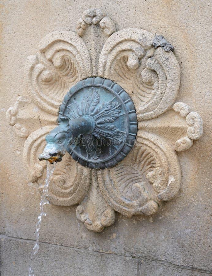 Fontaine traditionnelle corse avec de l'eau potable dans le mur en pierre photographie stock libre de droits