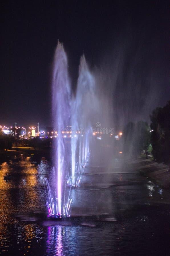Fontaines lumineuses colorées au milieu du lac la nuit image libre de droits
