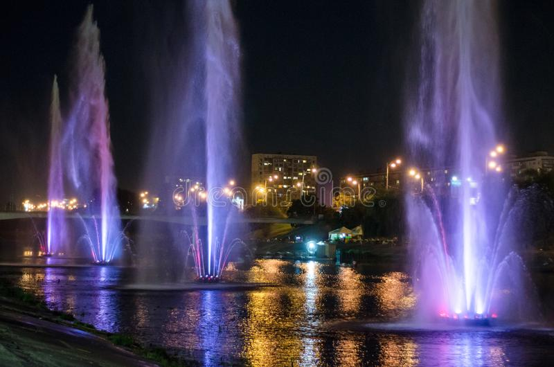 Fontaines lumineuses colorées au milieu du lac la nuit photo stock