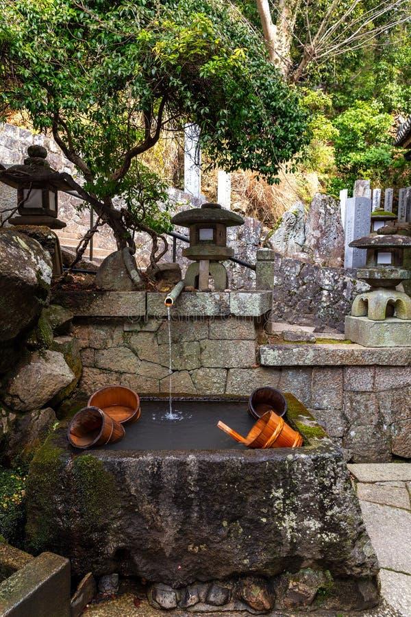Fontana con i secchi di legno dalla scala dell'entrata del tempio di Nigatsudo, parte di Todai-Ji a Nara, Giappone fotografia stock libera da diritti