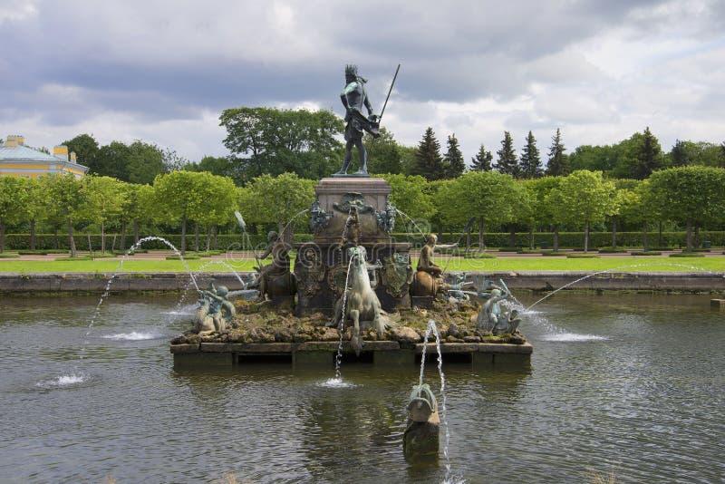 Fontana di Nettuno al di sotto di un giorno di estate tempestoso del cielo Peterhof immagini stock libere da diritti