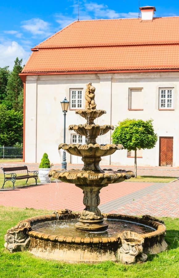 Fontana e costruzione di precedente granaio Chiesa cattolica Liskiava lithuania immagine stock libera da diritti