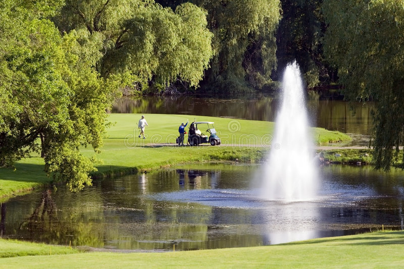 Fontana e giocatori di golf di terreno da golf fotografie stock