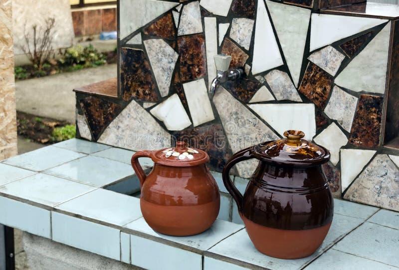 Fontana e vaso di argilla chiazzato immagine stock