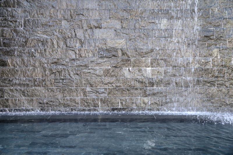 Fontana grigia della roccia che entra nello stagno fotografie stock