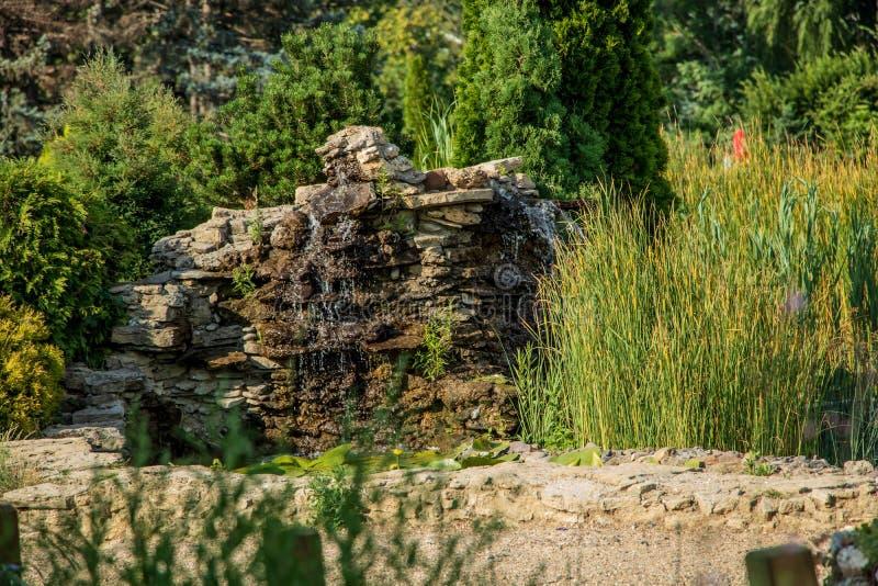 Fontana negli scorrimenti dell'acqua del parco attraverso le pietre fotografie stock libere da diritti