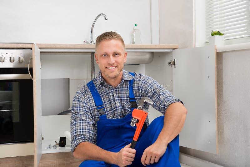 Fontanero With Adjustable Wrench en sitio de la cocina fotografía de archivo libre de regalías