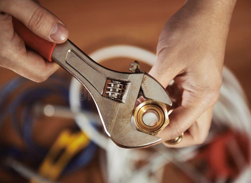 Fontanero con el tornillo imagen de archivo