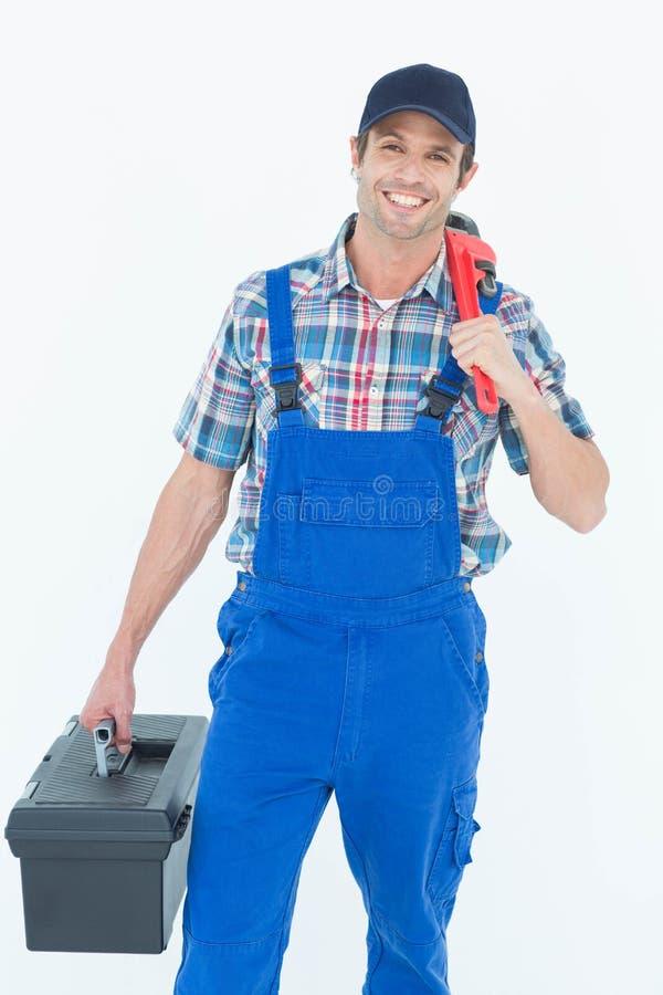 Fontanero con la llave inglesa y la caja de herramientas foto de archivo