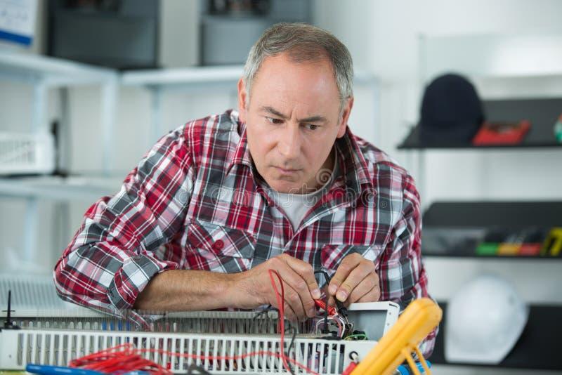 Fontanero de sexo masculino de la edad adulta media que repara el radiador imagenes de archivo