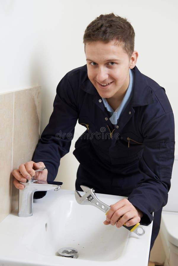 Fontanero de sexo masculino Working On Sink que usa la llave fotos de archivo libres de regalías