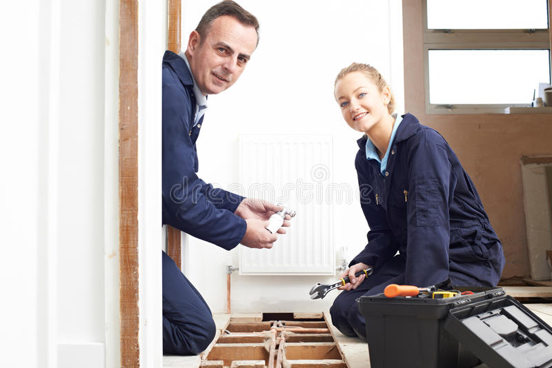 Fontanero And Female Apprentice que cabe el sistema de la calefacción central imagenes de archivo