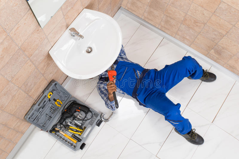 Fontanero Lying On Floor que repara el fregadero en cuarto de baño fotos de archivo