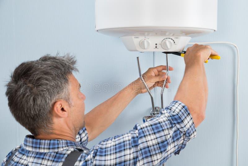 Fontanero que instala el calentador de agua imagen de archivo
