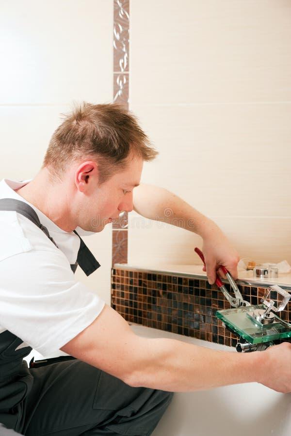 Fontanero que instala un golpecito de mezclador en un cuarto de baño foto de archivo libre de regalías